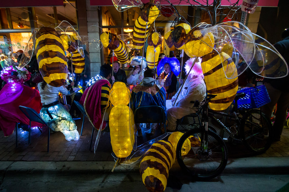 A group of people sit down to eat with their bee luminaries during the FoolMoon gathering on Friday, April 7, 2017. FoolMoon, part of a weekend of events, features beer gardens, music, art installations and luminaries made by hundreds in the crowd. Matt Weigand | The Ann Arbor News