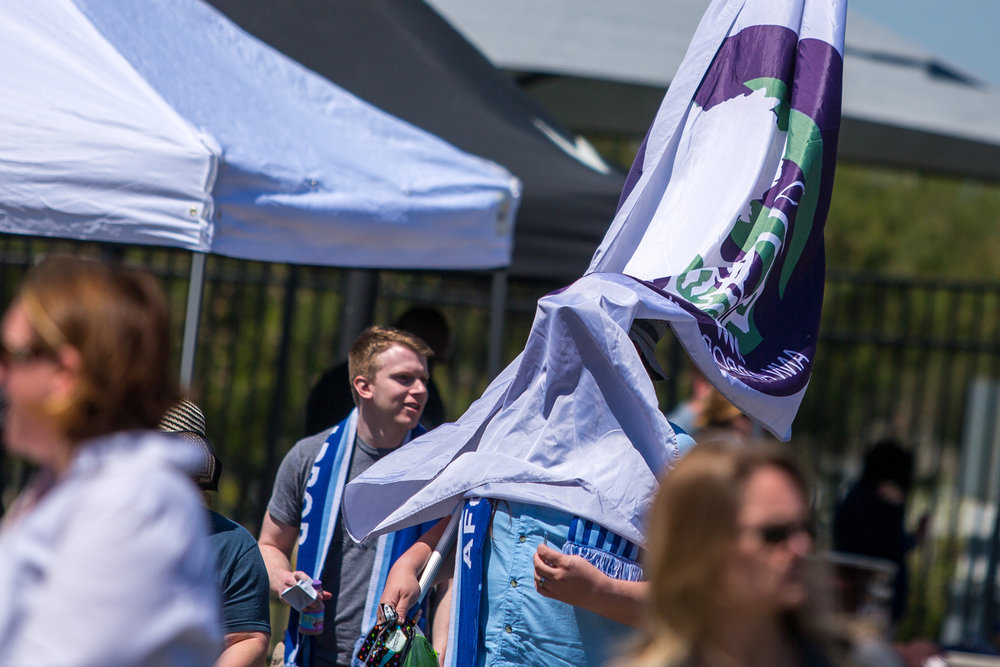 Matt Galardi's flag blows over his face as he arrives for the season opening National Premier Soccer League home opener between AFC Ann Arbor and Kalamazoo FC at Hollway Field at Pioneer High School on Sunday, May 14, 2017. Ann Arbor beat Kalamazoo 2-0, with goals in the 40th and 54th minutes. Matt Weigand | The Ann Arbor News