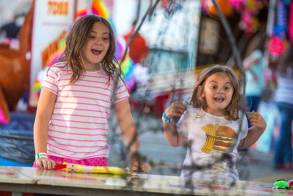 Kate Heller, 10, left and her sister Julianne, 7, celebrate after winning a prize during the opening day of the Ann Arbor Jaycees Carnival at Huron high School on Wednesday, June 21, 2017. The carnival runs from Wednesday to Sunday and over 30 rides and carnival games are available for all ages. Matt Weigand | The Ann Arbor News