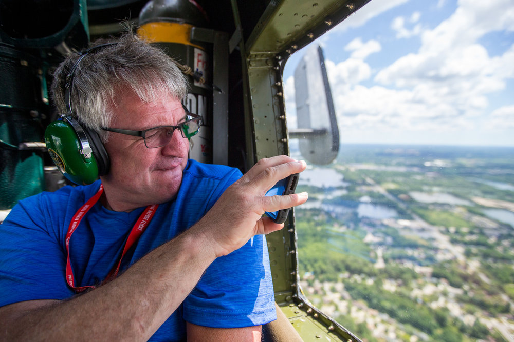 An individual takes a photograph from a window in a 1945 B-25 Mitchell Bomber on Saturday, June 24, 2017. StoryPoint Senior Living in Saline surprised their 99-year-old resident George Lusko with his dream of flying in the B-25. Lusko and his unit in World War II were credited with 27 shoot downs of enemy aircraft in a B-25 Mitchell Bomber.  Matt Weigand | The Ann Arbor News