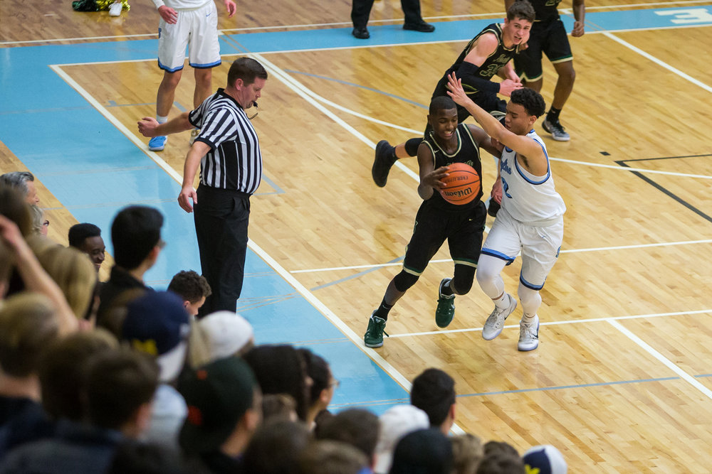 A Huron player battles against Skyline's Brandon Wade (2) to keep the ball inbounds during the first half of play against Skyline at Skyline High School on Friday, February 3, 2017. Skyline high School beat Huron high School 63-62. Matt Weigand | The Ann Arbor News