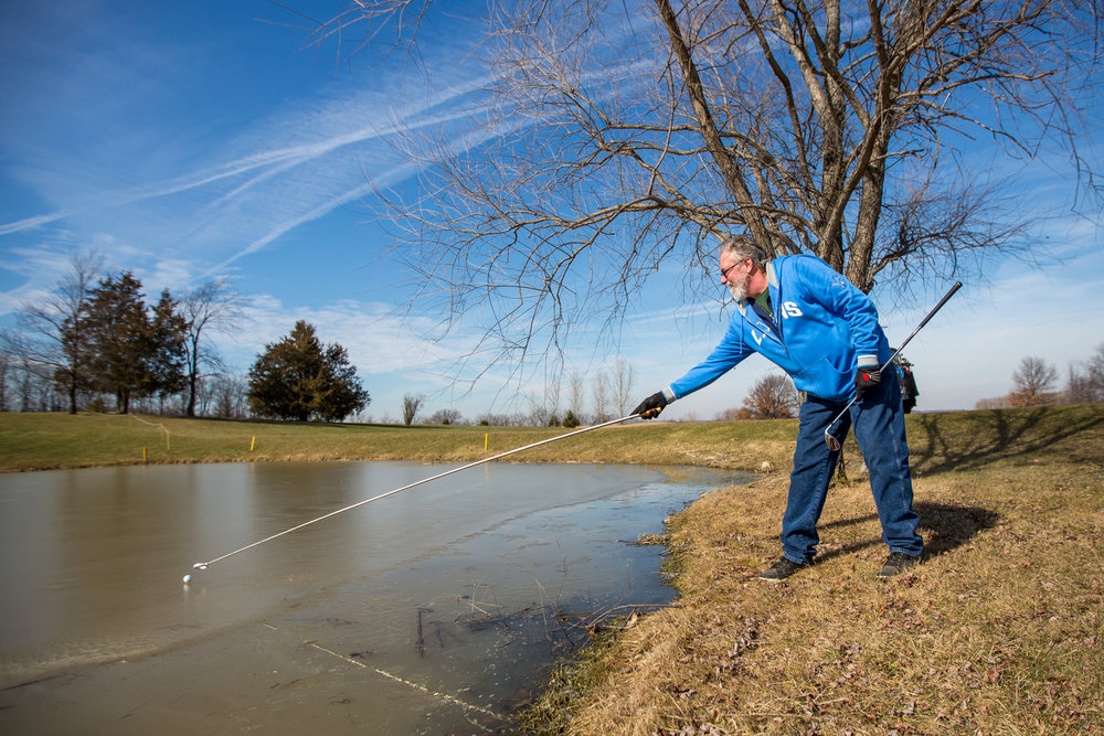 Rick Polmounter reaches for a ball that sits on the ice while golfing on the 15th hole at Rustic Glen Golf Club in Saline on Friday, February 16, 2017. Due to the unseasonably warm weather, local golf courses are beginning to open for golfing. Matt Weigand | The Ann Arbor News