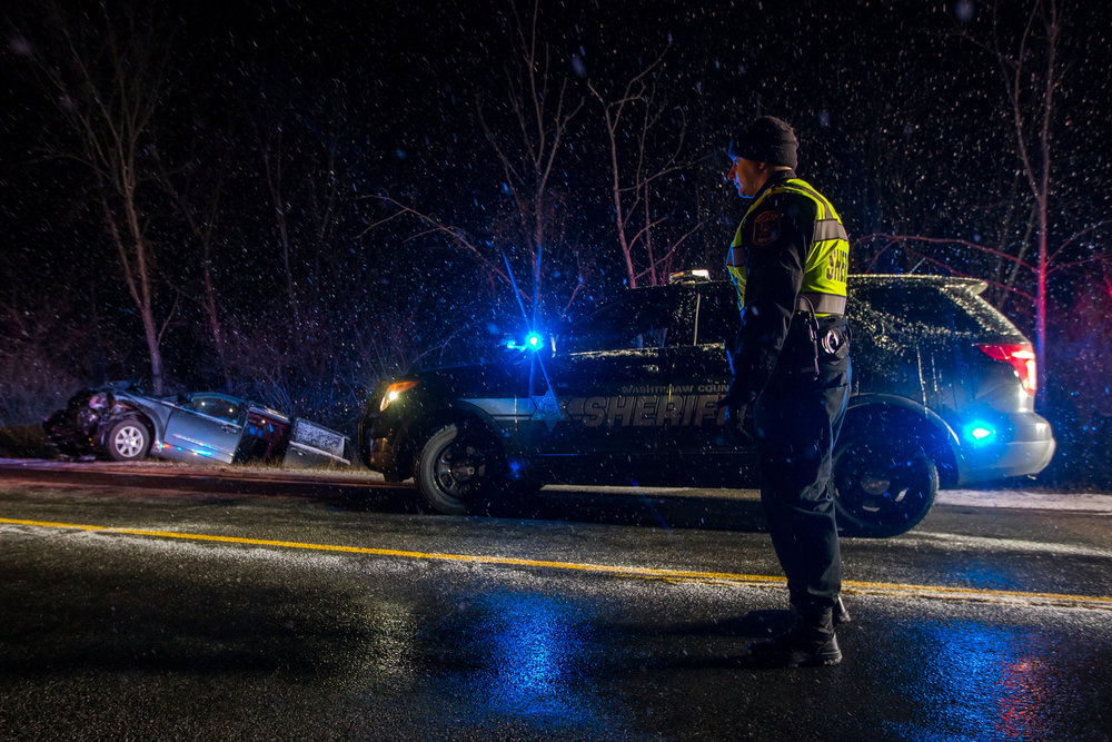 Deputy Johnny Woollams stands near a car that sits in the ditch on Prospect Road after being involved in a two car accident on Prospect Road near Cherry Hill Road on the evening of Thursday, March 2, 2017. The accident is still under investigation. Matt Weigand | The Ann Arbor News