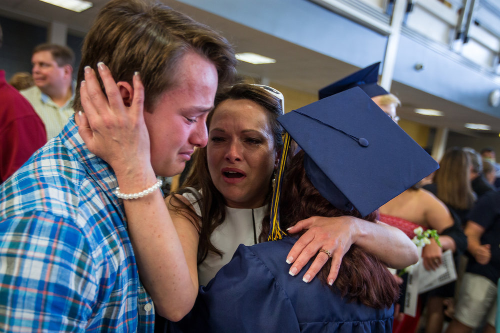 Sean Egan, left and Sandy Werth cry as they embrace Oak Marie Egan after the graduation ceremony at Chelsea High School on Sunday, June 4, 2017. Matt Weigand | The Ann Arbor News