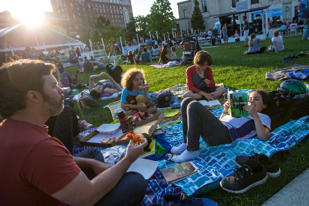 A family sits and enjoys music at Ingalls Mall for the opening night of Top of the Park, part of the Ann Arbor Summer Festival on Friday, June 9, 2017. The opening night featured yoga, multiple live music acts and food and drinks for all ages. Matt Weigand | The Ann Arbor News