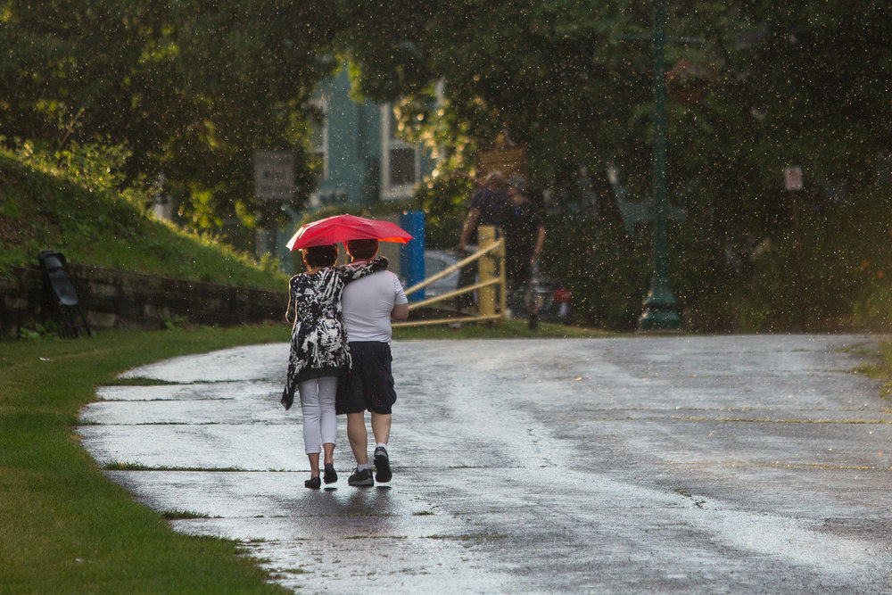 Two people walk with an umbrella during the 17th annual Michigan Elvisfest at Riverside Park in Ypsilanti on Friday, July 7, 2017. The festival features multiple Elvis tribute bands, vendors, kids activities and runs through Saturday, July 8. Matt Weigand | The Ann Arbor News