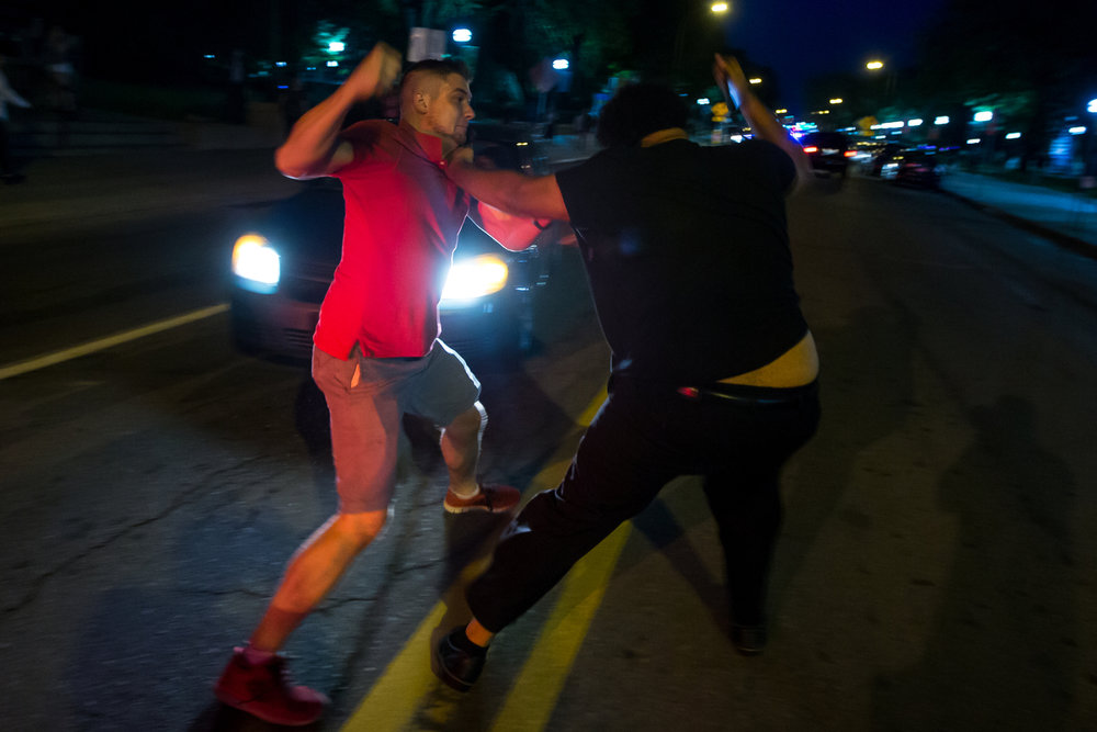 A University of Michigan sophomore, black shirt, fights with an individual, red shirt, while a group of protesters block the intersection of State Street and South University Street on Wednesday, September 20, 2017. The group organized at the Michigan Union to address the recent incidents of racism on campus. Matt Weigand | The Ann Arbor News