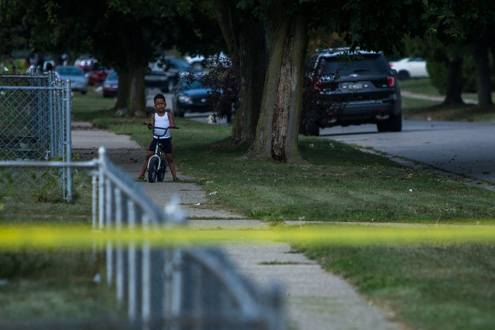 A young boy rides his bike as members of the Washtenaw County Sheriff department investigate a shooting was reported near 1366 Nash Avenue in the West Willow neighborhood on Monday, September 25, 2017. The incident is under investigation. Matt Weigand | The Ann Arbor News