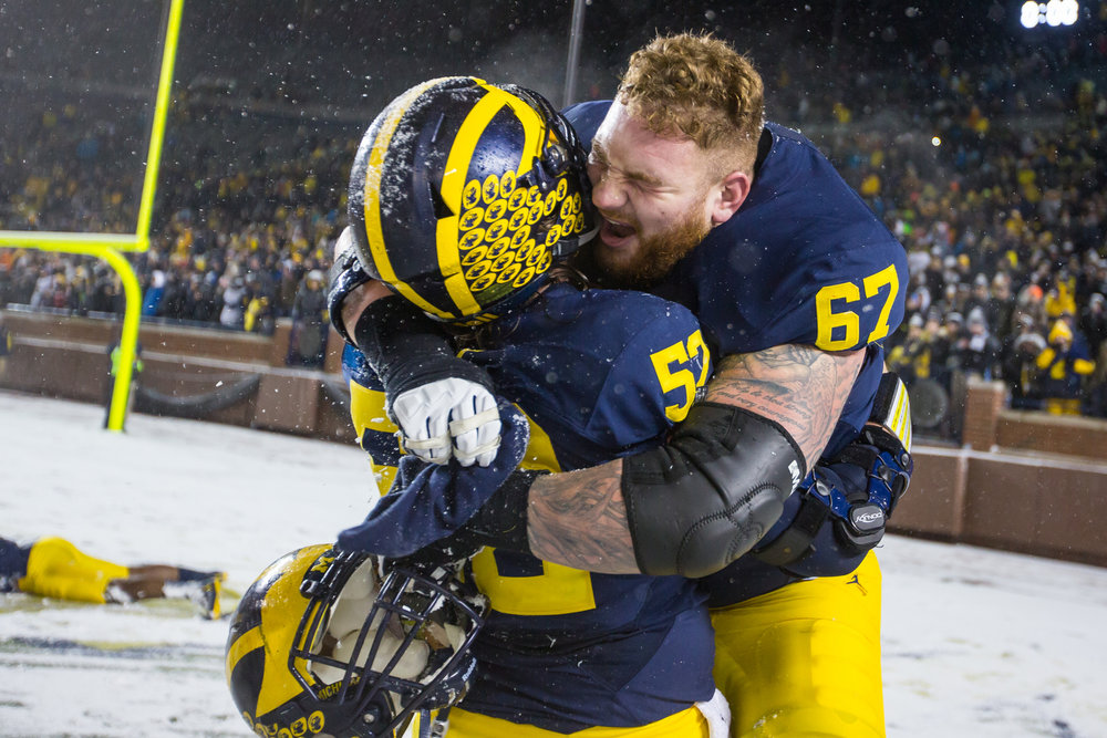 Michigan's offensive lineman Mason Cole (52), left and Michigan's offensive lineman Kyle Kalis (67) celebrate after the completion of the game between the Michigan Wolverines and the Indiana Hoosiers at Michigan Stadium on Saturday, November 19, 2016. Michigan beat Indiana 20-10.  Matt Weigand | The Ann Arbor News