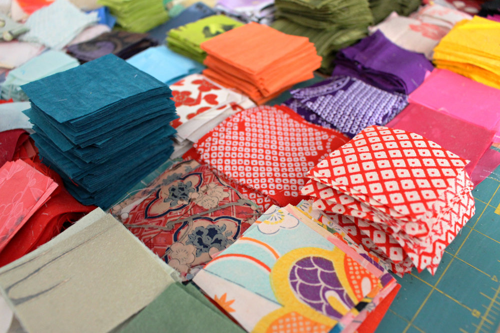 I cut and prepare all of my fabrics by hand. They are stored in piles just like this on a long table (not pictured) and await to be folded.