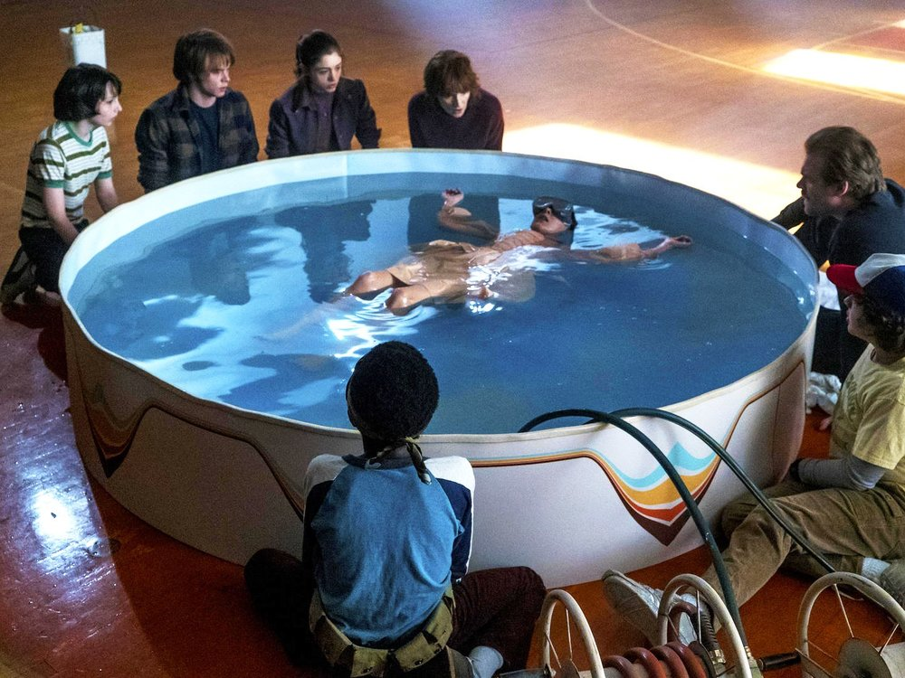 """Image from Netflix's """"Stranger Things"""", Eleven floating in sensory deprivation pool with goggles on while friends and family gather around for support and to ensure safety"""