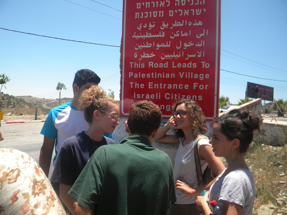 Windows' youth at the entrance to Beit Ommar, in area B, north of Hebron (2013).  At the entrance of all villages in area B and at the entrance to Area A, big red signs warn Israelis not to enter. The young journalists realized that the sign said entrance is dangerous, not forbidden, and chose to enter the village with their local peers.