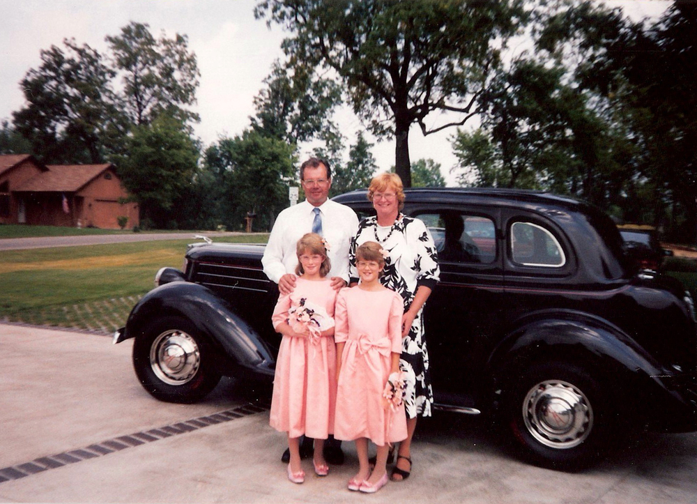 My dad (Bob), mom (Bonnie) me (Beth) and twin sister (Sue) circa 1990 standing in front of the 1936 Ford he restored when he was a teenager.