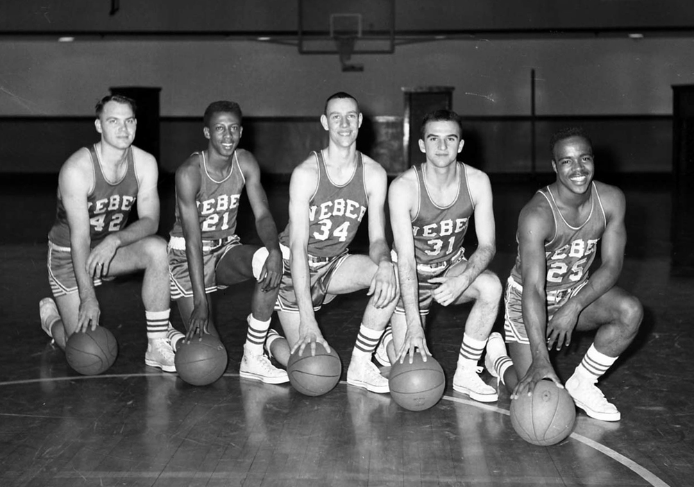 "Despite a great basketball season, Holmes (second from the left) faced difficult situations as the team travel across the Western United States. At times the team would need to stay in motels 40 miles away from their games because locations closer wouldn't allow entrance to African Americans. Holmes told me in his interview, his teammates supported him throughout this time. ""If they wouldn't serve me, we all got up and left"" he said."