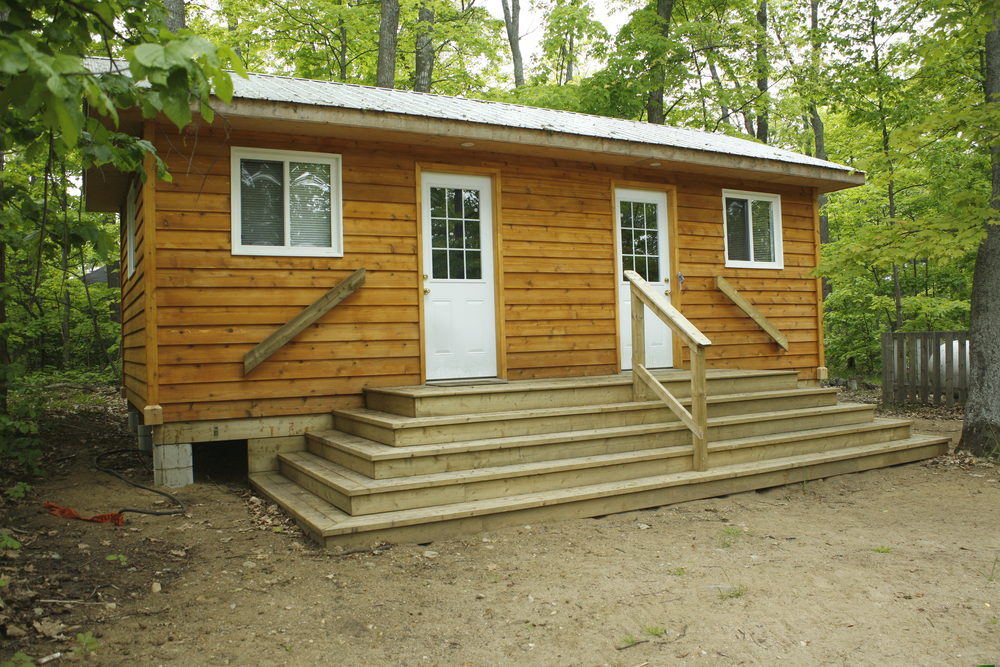 wooden cabin with two white doors and wide concrete steps