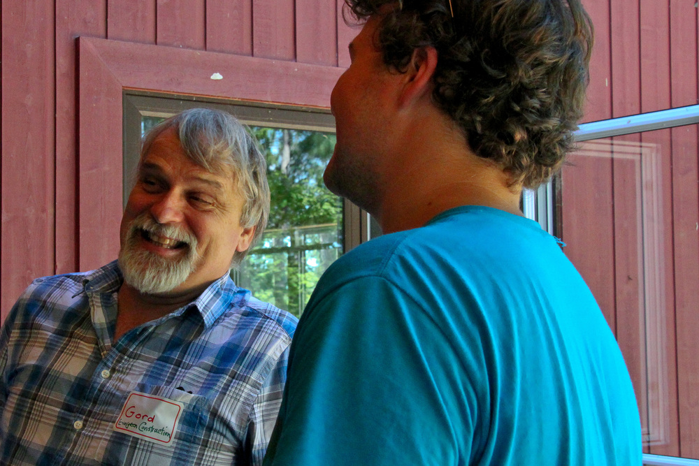 middle aged man with grey hard in plaid shirt smiling while talking to a middle age man with brown hair in blue tshirt inside a barn house