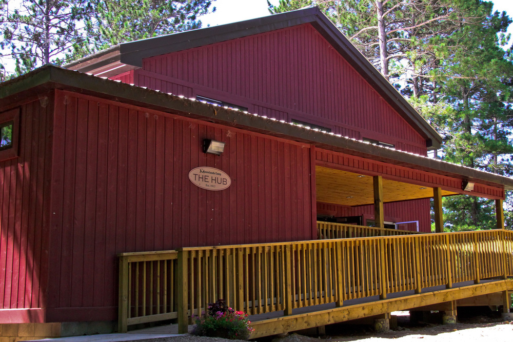 side view of red camp house with wooded railing extending to the front of the house