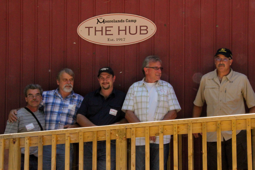four mean standing in front a red exterior house under a Moorelands Camp The Hub sign