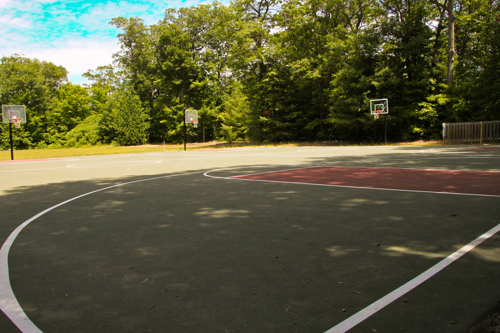 outdoor basketball court on campgrounds surrounded by trees