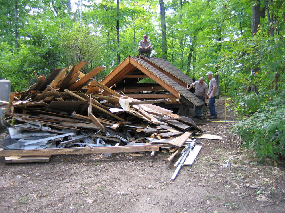 large pile of wood, materials, and leftover roof from a deconstruction project