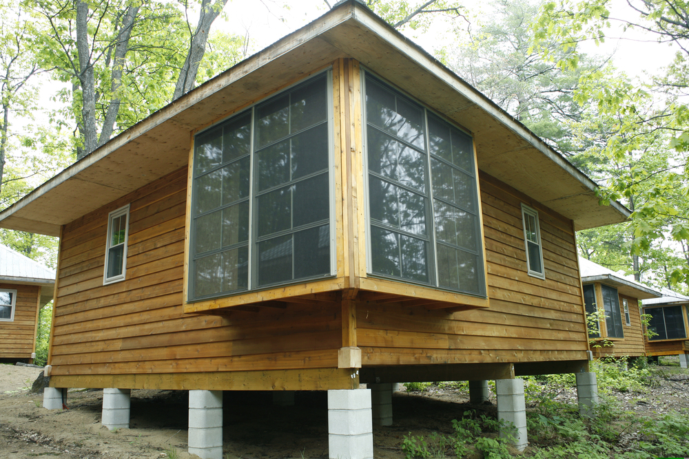 wooden cabin slightly elevated on concrete pillars with two large corner windows