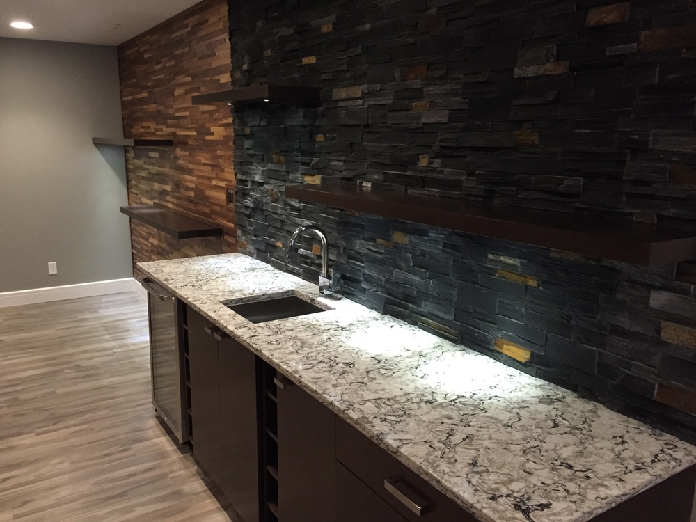 Basement renovation saskatoon, wet bar, stone work, custom shelves, trusted contractor.