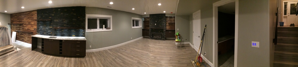 Basement renovation saskatoon, flooring, fireplace, stone work, custom shelving, trusted contractor.