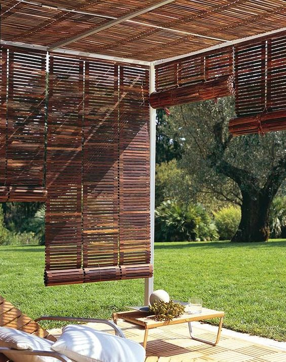 These wooden roll-up Venetian blinds are perfect to tie any patio in and make it its own individual space. Notice the wooden chaise lounges and deck tiles. Against the green grass (freshly cut!), it's like a little resort in your own backyard. Roll them up when you want to watch the kids toss the dog's frisbee or play with the Slip 'n' Slide (or when there's stormy weather). Roll them down when you want a little privacy and some shade from that hot, hot sun.