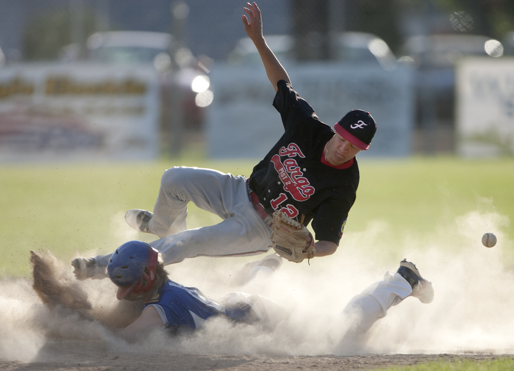 Fargo shortstop Jake Salentine dives for a catch in attempt to tag East Grand Forks' Hunter Aubol, as he slides safely into second base during a game at Stauss Field in East Grand Forks, Minn. on June 13, 2013. East Grand Forks Legion Post 157 lost to Fargo Legion Post 2, with a final score of 3-6.