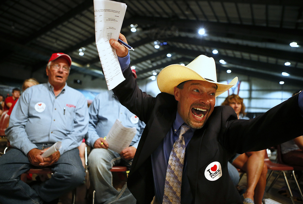 Auctioneer Todd Woodruff shouts and waves his arms wildly after Steve Rausch and Associates bid the high price of 80,000 dollars for the grand champion market steer at the Sale of Champions, Sunday, August 3, 2014, in the Celeste Center at the Ohio State Fair.
