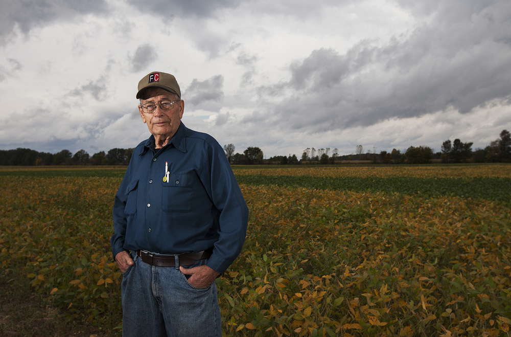 Bill Cox poses for a portrait in front of his field of soy beans outside of his Ostrander home, Friday, October 3, 2014.