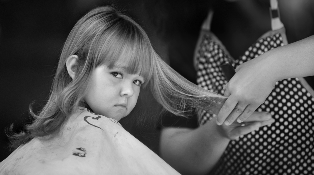 "Abby Joseph, 3, stares through the front window of ""Just Around the Corner Hair Salon"" in Hyden, Ky. on Oct. 12, 2013, patiently waiting to see her feminine new hair-do."