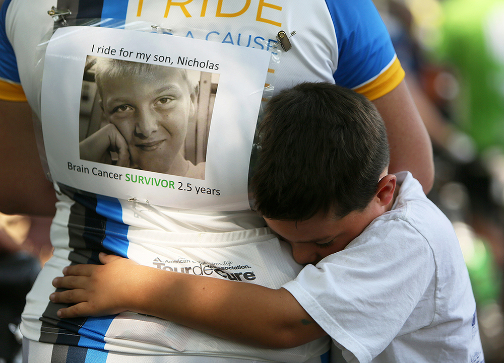 Matthew Sawchuk, 7, embraces his mother Jennifer Sawchuk, at the finish line of the Pelotonia 100-mile cancer awareness ride, Saturday, August 9, 2014, in Columbus, Ohio. Jennifer rode for Matthew's brother, Nicholas Sawchuk, 13, who is a two-and-a-half year survivor of brain cancer.