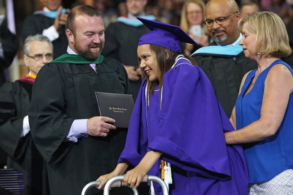 Macy Huff walks the stage to receive her diploma with help from a walker and physical therapist Kim Deckman (right), during Ben Davis High School graduation, Saturday, June 4, 2016. Huff surprised her classmates and received a standing ovation when she rose from her chair.