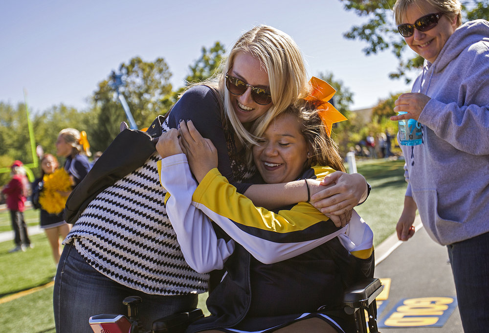 Makenzie Bishop hugs Macy during the Grizzlies homecoming football game. Bishop and Huff, who graduated from Ben Davis High School together in June, have been best friends since grade school. Bishop now attends Purdue University and surprised Huff during the game.