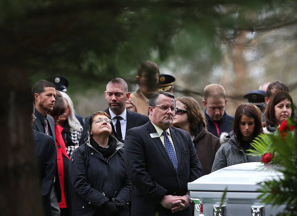 Loved ones gather for the burial of former Indianapolis Fire Department chief Brian Sanford, Friday, March 25, 2016, at Crown Hill Cemetery, Indianapolis, Ind. Sanford, 59, died Monday after battling Lou Gehrig's disease.