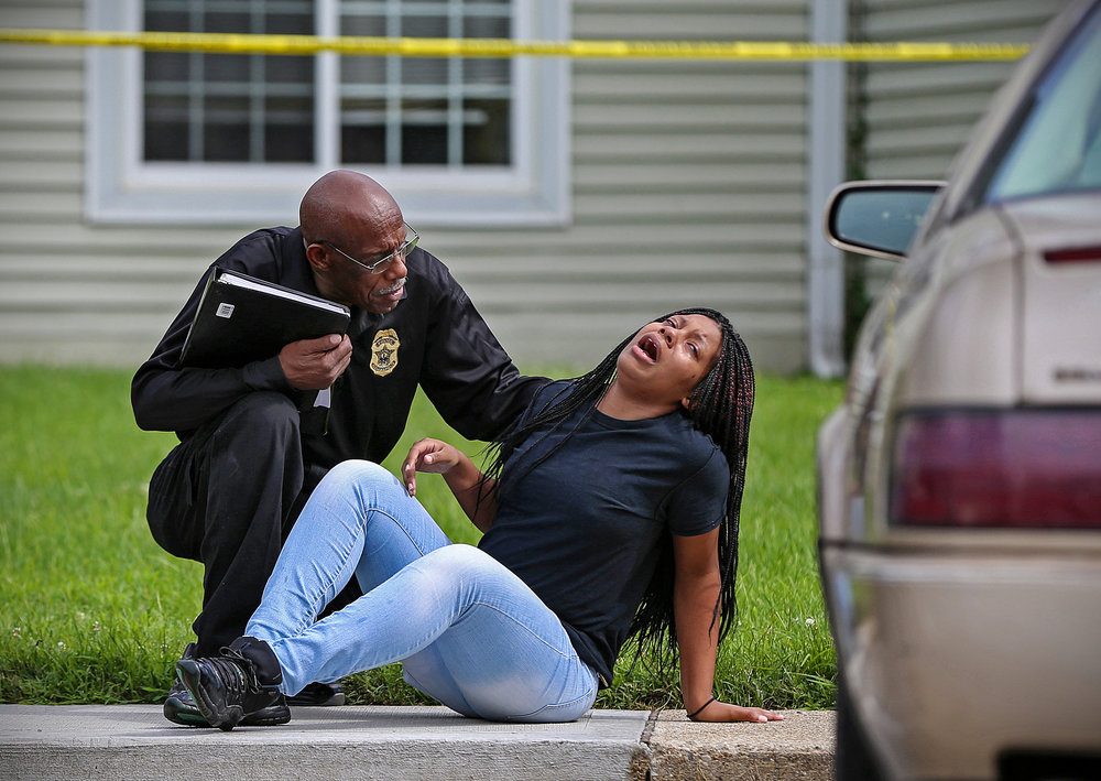 "A loved one reacts at the scene of a triple murder at an apartment on Admar Court near 46th Street and Binford Boulevard, Indianapolis, July 22, 2016. An infant girl was found sleeping in the apartment, unharmed, though her parents Cameron Baker, Takara Coleman, and an upstairs neighbor, Lisa Woods, were found dead. ""That's my best friend,"" the girl shouted before dropping to the side walk."