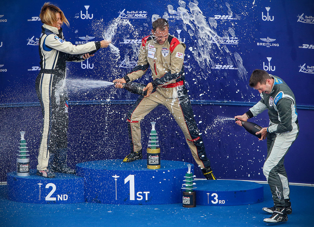 From left, Challenger Cup winners Melanie Astles, Luke Czepiela and Ben Murphy celebrate with champagne after the Red Bull Air Race at Indianapolis Motor Speedway, Sunday, October 2, 2016.