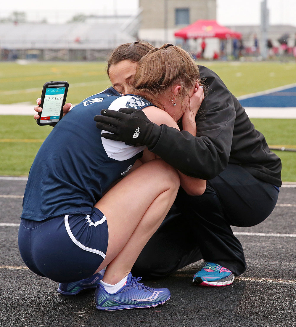 Perry Meridian's Kayla O'Brian is comforted by Perry Meridian distance coach Laura Schroeder at the finish line of the 3200 meter run, at the IHSAA girls track and field sectional at Decatur Central High School, Indianapolis, Tuesday, May 17, 2016. O'Brian placed fifth in 12:14.17, but only those who place in the top three advance to IHSAA regionals at Ben Davis High School, May 24, 2016.