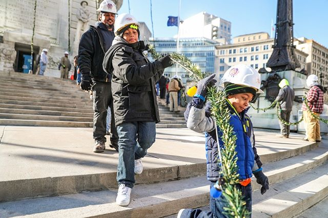 """From left, Antwaun Armstead, his sons Amarius, 8, and Azon, 4, and other union electricians from IBEW local 481 work to string 52 garland strands of 4,784 holiday lights on the Soldiers and Sailors Monument in downtown Indianapolis this morning. The annual Circle of Lights """"tree"""" lighting is held the day after Thanksgiving, this year on Nov. 23, 2018. (Photo by @Jennajulyaugust)"""