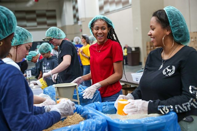 Jordyn Holder (middle), and Shanyah Sears, both Decatur Central High School students, pack dried vegetables and rice into meal bags during the 8th annual Million Meal Marathon at Lucas Oil Stadium in Indianapolis on Tuesday. Today, more than 3,000 volunteers aim to pack 1 million meals for the hungry in Indiana. (Follow the photographer  @mykalmceldowney)