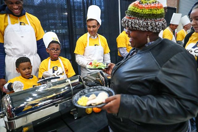 """Indiana Pacers small forward Thaddeus Young (left) helps his sons, Taylor and Thaddeus Jr., serve food to Marquita Bright during the 21st annual Come to Our House Thanksgiving Dinner, an event part of the Pacers Season of Giving, at Bankers Life Fieldhouse on Wednesday. """"I was the one feeding the homeless at MLK last year,"""" Bright said. """"My husband and I are the example of you're one paycheck away from being homeless."""" (Follow the photographer  @mykalmceldowney)"""