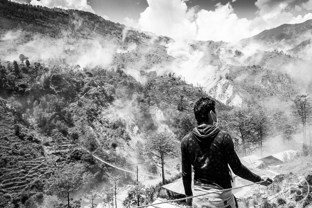 Un homme regarde les glissements de terrain au loin.