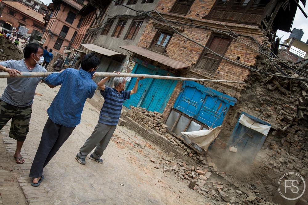 Des équipes mettent à terre des maisons presqu'effondrées.