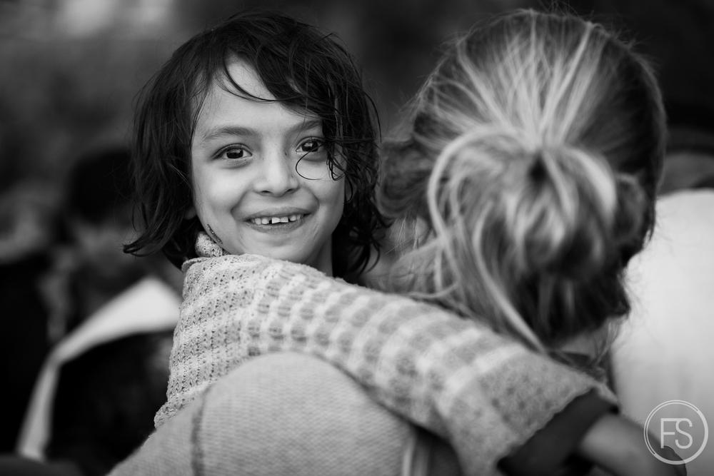 Une jeune fille est transportée en sûreté à après être débarquée de son bâteau sur l'ile de Lesvos.