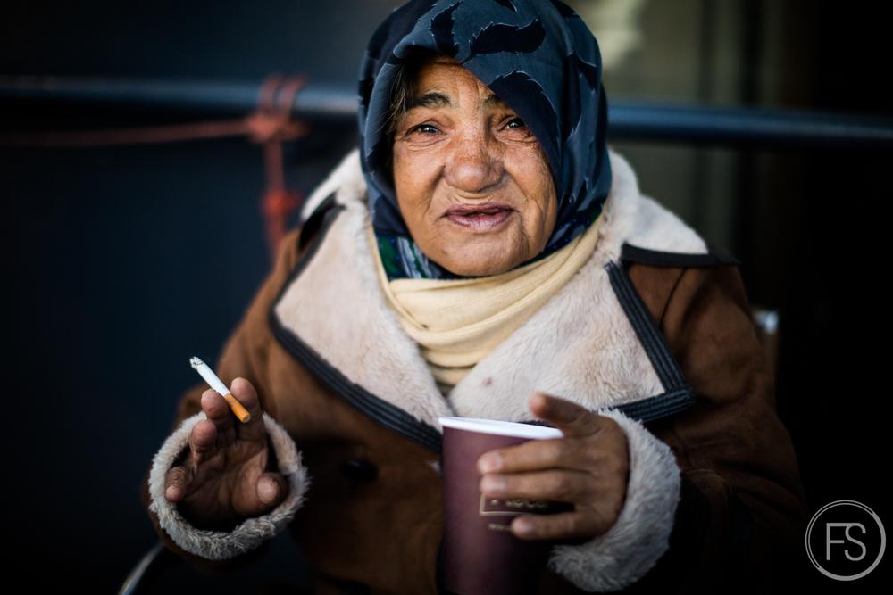 Une dame sourit au photographe en prenant sa cigarette matinale sur le traversier juste avant d'arriver à Athènes.
