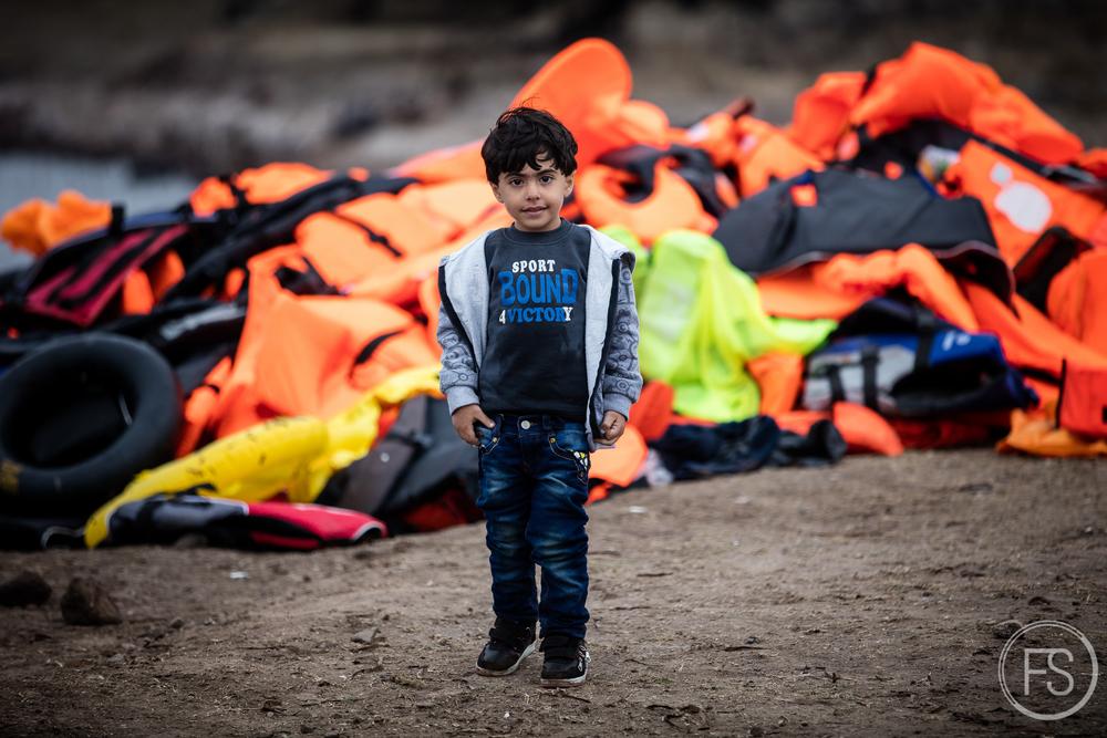 Un jeune garçon vient d'arriver sur l'ile et pose devant une montagne de gilets de sauvetage délaissés sur les rives.