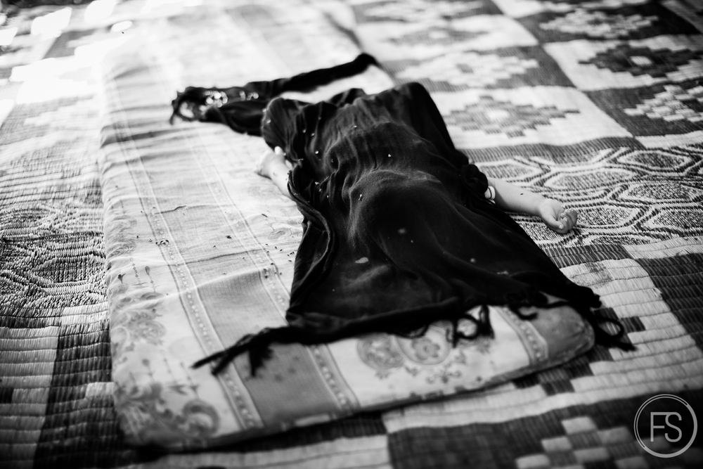 A baby sleeps on the carpet in the middle of a tent. The shawl covers him from the flies around.Akkar District, Lebanon