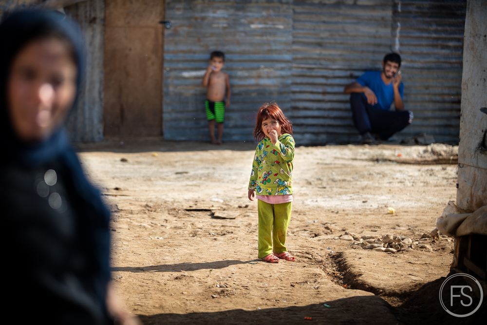 Among her relatives, a little girl smiles at the camera. Around 20 families live in the camp that has been reestablished in this location for one year.Akkar District, Lebanon