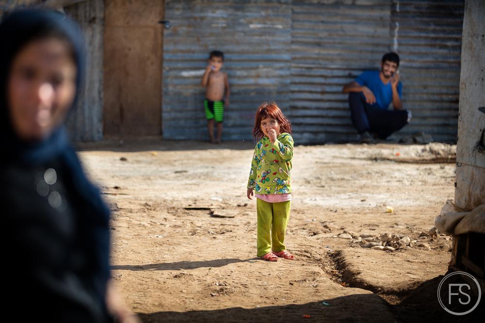 Entourée de sa famille, une jeune fille sourit à la caméra dans un camp de réfugiés du district d'Akkar dans le nord du Liban. Une vingtaine de familles habitent dans ce camps depuis plus d'un an.